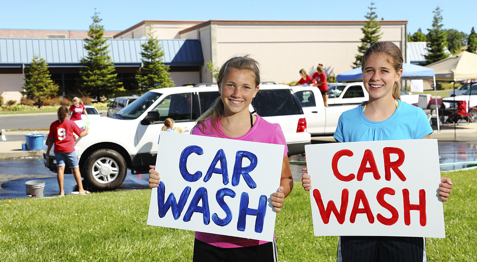 School kids running a car wash fundraiser