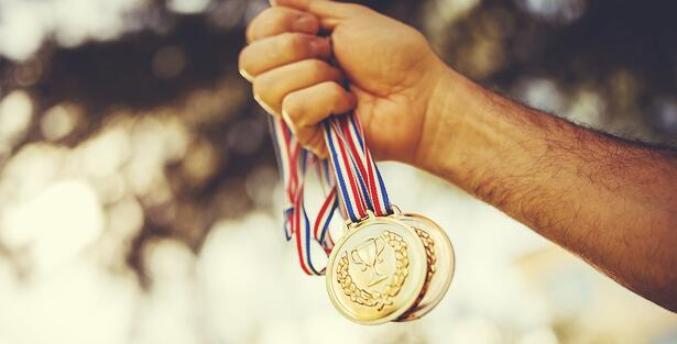 Man holding gold medals