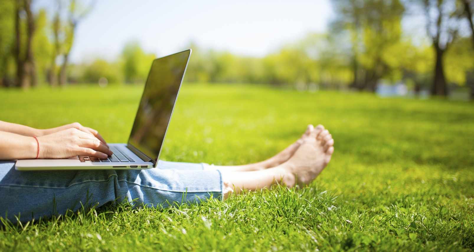 Woman working on laptop computer outside