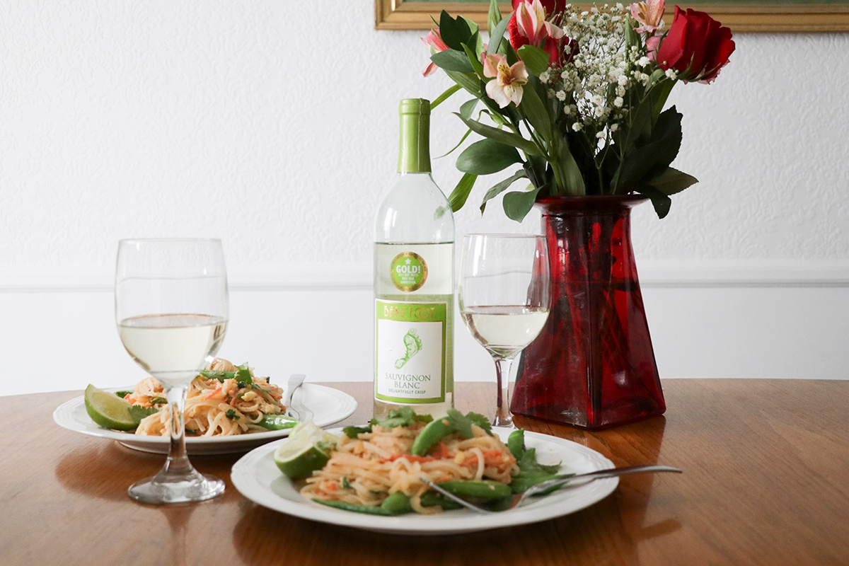 Chicken Pad Thai and Sauvignon Blanc on dining room table by a vase of flowers