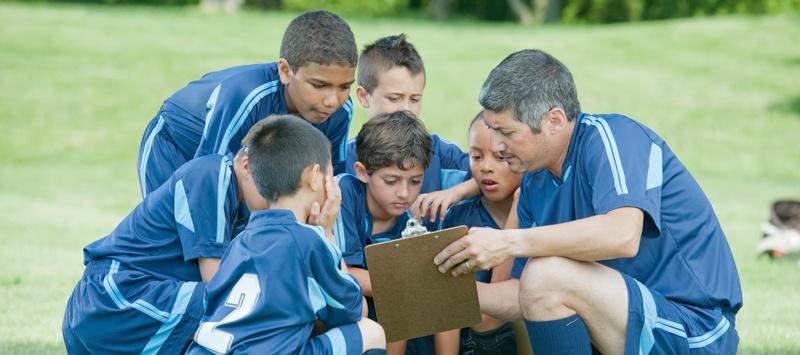 boys soccer team huddled around the coach