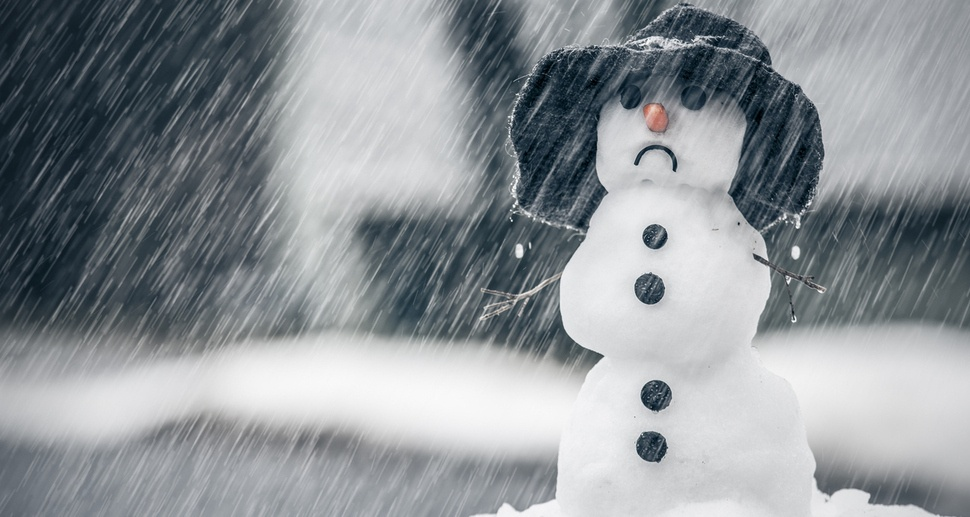 Sad snowman frowning in the rain and snow