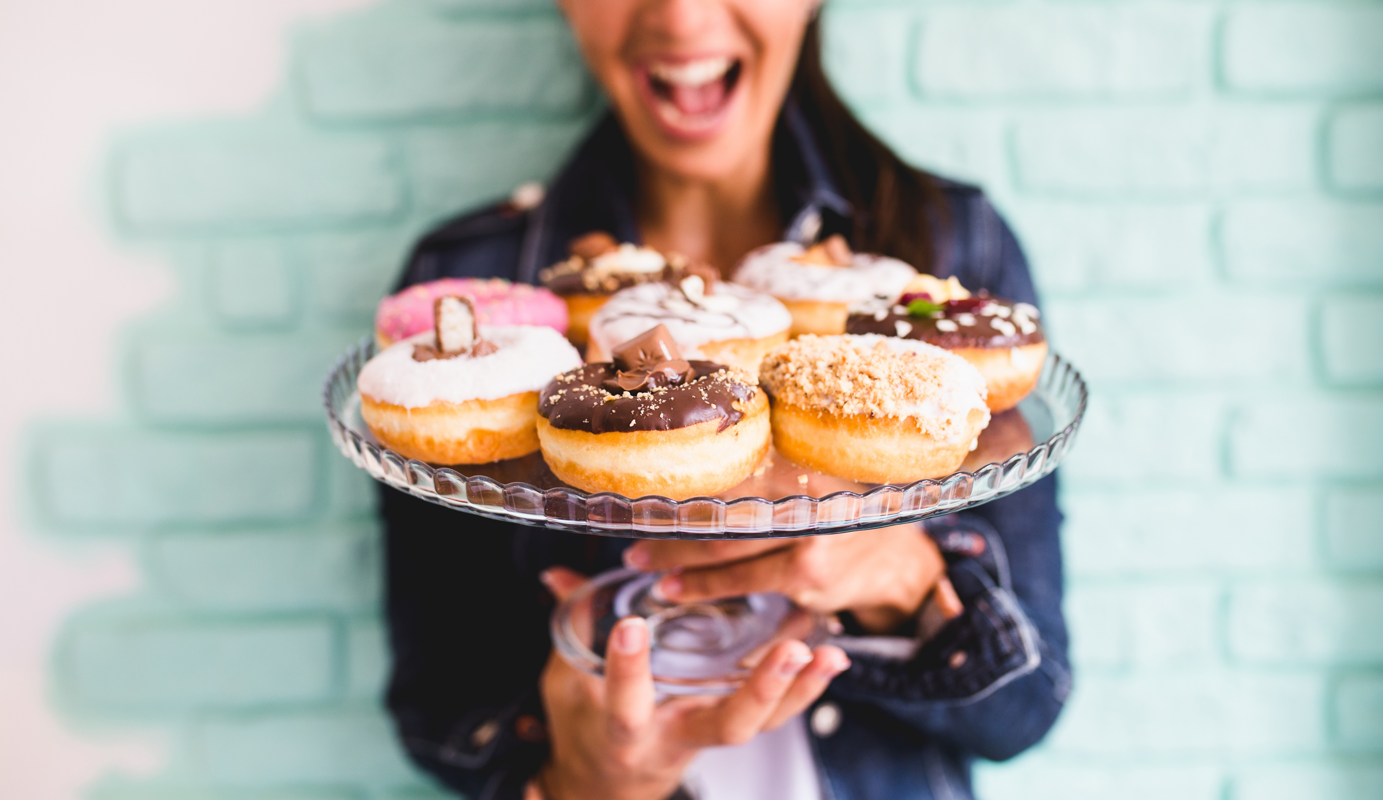 ecstatic_woman_holding_plate_of_donuts.jpg