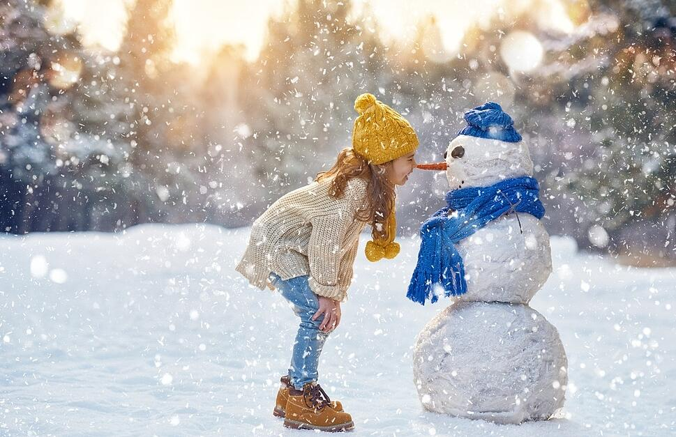 girl_playing_with_snowman_in_winter