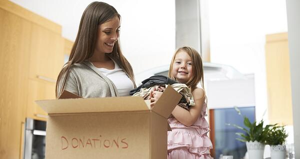 Mom and daughter donating clothes