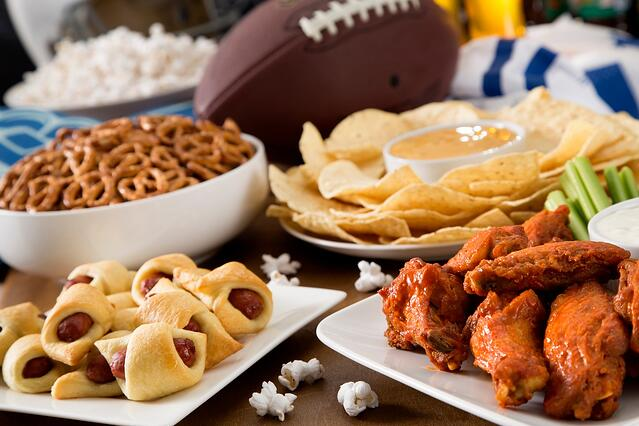 Pretzels, pigs in a blanket, wings, and tortilla chips on a table for the Super Bowl