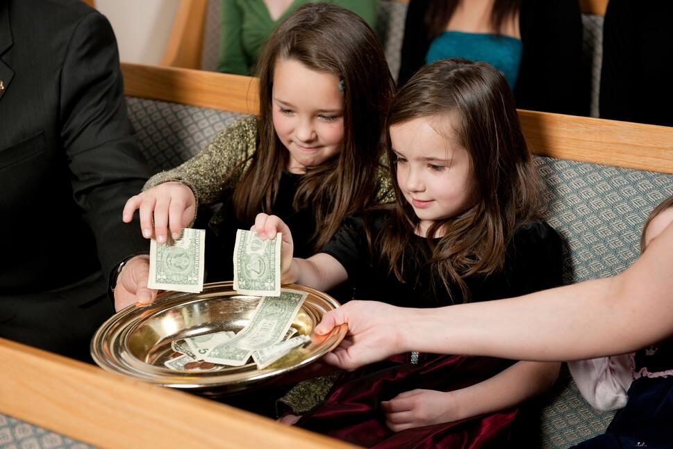 Little girls placing money in the offering plate at church