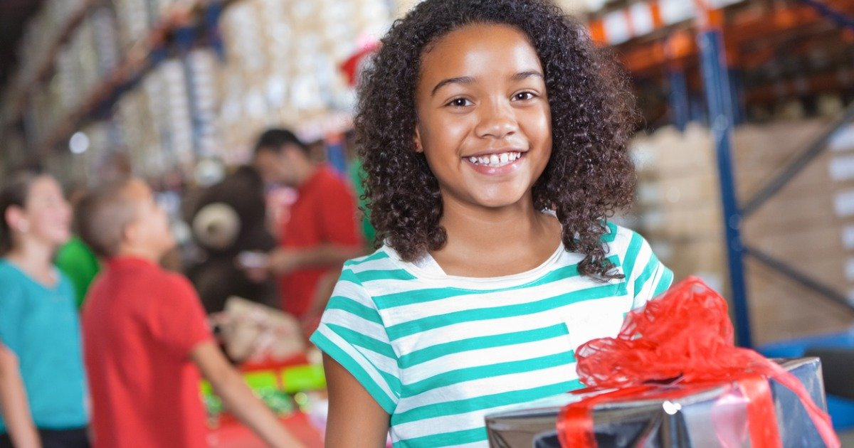 happy-little-girl-donating-christmas-gifts-at-charity-toy-drive-picture-id175380504