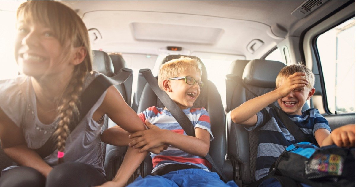 happy-playful-kids-travelling-by-car-picture-id1153359710