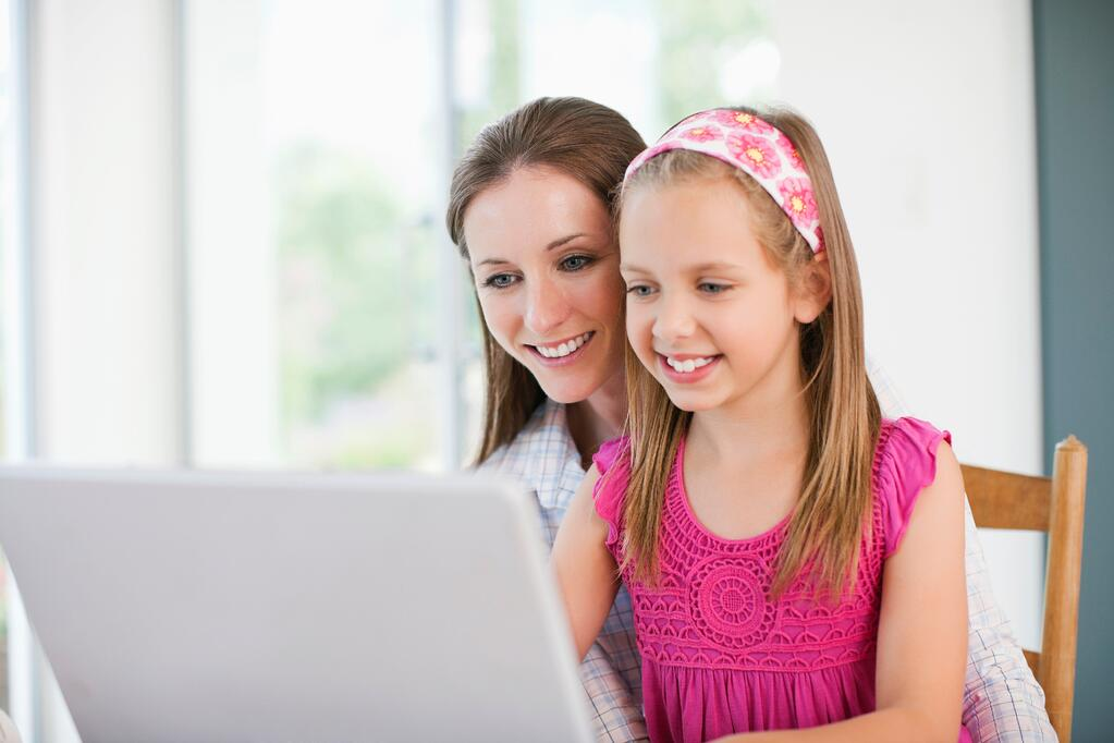 Mother and daughter happily working on computer