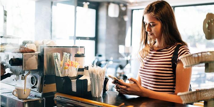 millennial-woman-at-paying-coffee-shop-counter-picture-id1151056727